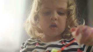 Portrait of beautiful caucasian little girl with blond curly hair making bubble blower and looking on the camera on home background. Indoor.