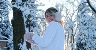 Portrait of beautiful happy girl in frosty winter park. Outdoors. Flying snowflakes, sunny day. backlit. Smiling to camera, joyful cheerful mood,emotions
