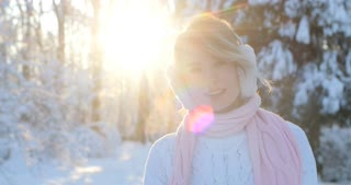 Portrait of beautiful happy girl with ear muffs, in frosty winter park. Outdoors. Flying snowflakes, sunny day. backlit. Smiling to camera, joyful cheerful mood,emotions