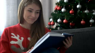 Portrait of beautiful woman wearing stylish christmas tree sweater and reading a book sitting on comfortable sofa. Close up.