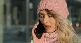 Portrait of charming girl answering call, talking on the smart phone, walking on street. Enjoying snowfall, expressing positivity, joyful cheerful mood, new year mood