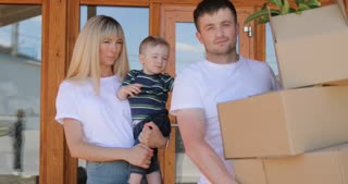 Portrait of couple and their little son, carrying cardboard box moving into the new modern home. Couple moving to a new home, rent house