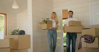 Portrait of couple carrying cardboard box into the new modern home to the living room. Couple moving to a new home, rent house
