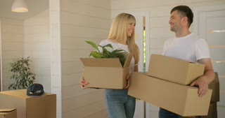 Portrait of couple carrying cardboard box into the new modern home to the living room. Couple moving to a new home.