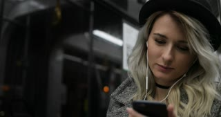 Portrait of cute girl in black hat listening to music and browsing on mobile phone in public transport. City lights background