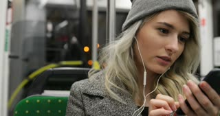 Portrait of cute girl in headphones listening to music and browsing on mobile phone in public transport. City lights background