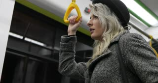 Portrait of cute young woman wearing a black hat answering incoming call in public transport. Someone calling