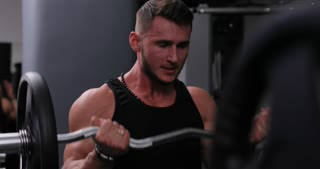 Portrait of fit man in sportswear lifting heavy weights during a workout session in a gym. Man exercising hardly with sport equipment in a gym. Sports and fitness concept