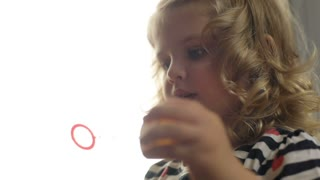 Portrait of pretty caucasian little girl with blond curly hair making bubble blower on home background. Indoor.