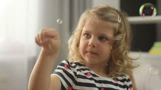 Portrait of pretty little girl with blond curly hair and blue eyes in home playing with bubble blower. Indoor.