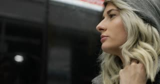 Portrait of pretty young blond girl in warm hat and jacket riding on public transport at night. She feel cold