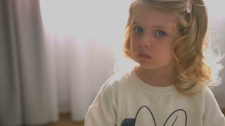 Portrait of serious caucasian little girl with blond curly hair and blue eyes looking on the camera on home background. Indoor.