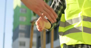 Portrait of shaking hand of two construction workers in green uniform at the bulding object. Outdoor.
