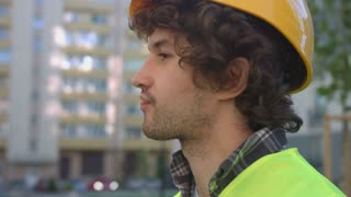 Portrait of side view of caucasian young builder with black curly hair in the protective helmet, looking up. Outdoor.