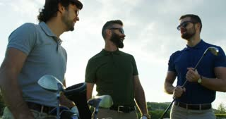 Portrait of three male golfplayers talking and looking at the golf club on the nice sunny day. Outside