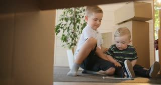Portrait of two little boys having fun - playing or reading from tablet at their new house. Brothers are interested using and play digital tablet. Education, mortgage, housing and real estate concept.