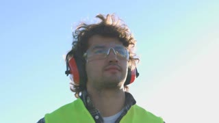 Portrait of young builder with black curly hair in protected glasses and headphones looking around. Outdoor.
