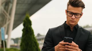 Portrait of young business man in the glasses in the stylish black shirt using smart phone on the airport background.