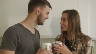Portrait of young couple in love drinking morning and smiling at the white kitchen.
