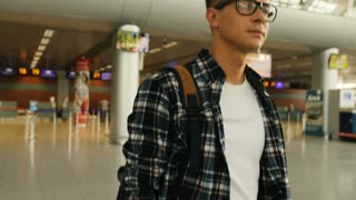 Portrait of young handsome man in the glasses with the baggage walking from the plane in the modern airport terminal. Dolly shot. Close up.