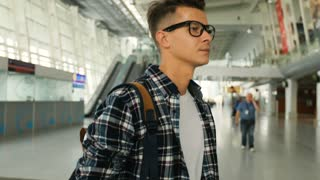 Portrait of young man in the glasses with the baggage walking in the modern airport terminal and searching his plane. Dolly shot. Close up.