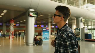 Portrait of young man with glasses checking his flight from the arrivals table in the airport.