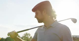 Portrait shot of attractive male golf player in the sunglasses with a club smiling straight into the camera and touching his glasses. Outside. Close up