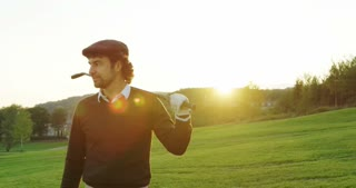 Portrait shot of attractive man posing to the camera with a club on his shoulder, golf pitch background. Outside