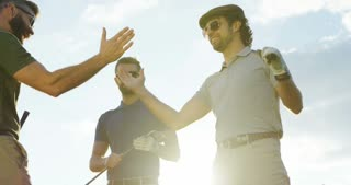 Portrait shot of male friends with golf clubs meeting outside and shaking hands. Sunny sky background