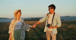 Portrait shot of the romantic young couple in love walking hand in hand in the field and kissing. Summer sunset.