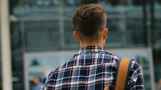 Portrait shot of young man walking to the modern airport terminal for his flight. View from the back. Close up.
