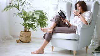 Pretty girl drinking coffee or tea and relaxing in chair, reading a book