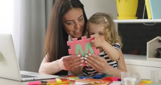 Pretty little girl with blond curly hair with her mother sculpting with plasticine on the living background. Indoor.