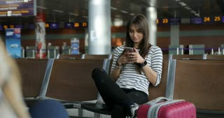 Pretty young girl smile while using smartphone to read internet news