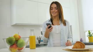 Pretty young woman in the kitchen calling her friend using smart phone