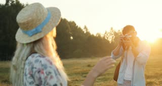 Rear of the young blonde woman posing to the Caucasian man, photographer taking photos on the camera. Photoshoot in the field on the sunset.
