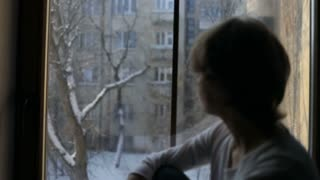 Sad female looking out the window,and think about something, broken-hearted
