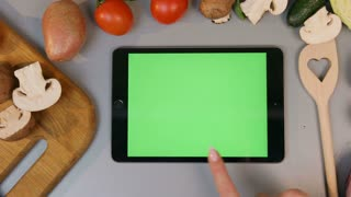 Scrolling throught tablet in the kitchen. Vegetables are on the background.