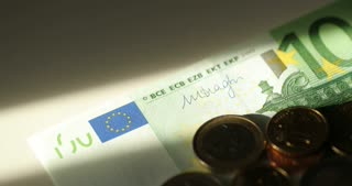 Seamless looping of a bunch of banknotes rotating on a plate with shallow depth of field. 100 Euro bills. Euro currency. Coins stacked on each other in different positions