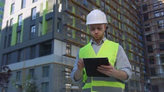 Serious caucasian builder with white protected helmet and green safety vest using tablet on unfinished construction background.