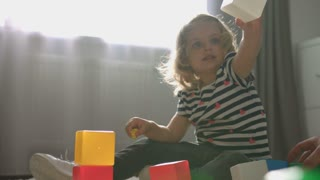Side view of caucasian charmind little girl with blond curly hair siting on the floor in home and playing with cubes and little toy. Indoor.