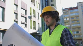 Side view of young builder in yellow protected helmet and vest looking drawing on unfinished construction background.