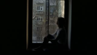 Silhouette of woman sitting on the windowsill and looking out the window
