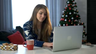 Smiling young woman typing laptop on the christmas tree background in the living room.