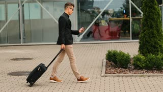 Stylish young business man with the baggage walking to the airport terminal while typing in the smart phone.