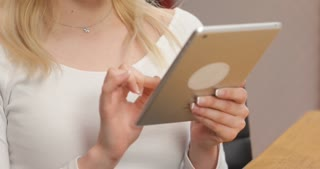 Successful business woman working at the office. Gorgeous young businesslady in glasses at her workplace using tablet computer
