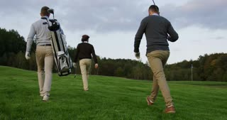 Three men with clubs and golf bag walking on the golf fied. Back view from below. Outside