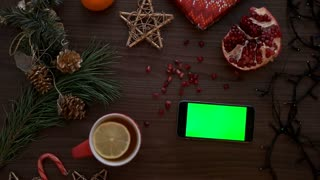 Top view man hand using mobile phone with green screen. Finger scrolling pages on touchscreen. Christmas details on wooden table background. Chroma key. Horizontal smart phone