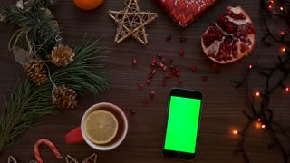 Top view man hand using smart phone with green screen. Finger scrolling pages down on touchscreen. Christmas details on wooden table background. Chroma key
