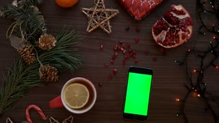 Top view man hands tapping on a smart phone touchscreen with green screen. Christmas decor on the wooden table background. Chroma key. Shot from above